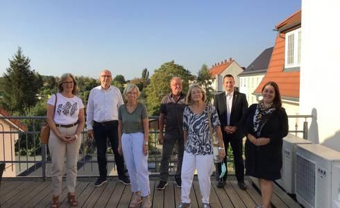 (Foto: v.l.n.r: Reinhild Lehmann, Dirk Michaelis, Elisabeth Hoppe, Dieter Thiel (für Melanie Dürichen), Karin Deliga, Matthias Zander, Dorothée Vatterott mit Abstand auf dem Balkon der SWB)